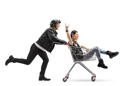 subculture: Biker pushing a shopping cart with a punk girl riding inside and making a rock sign isolated on white background Stock Photo
