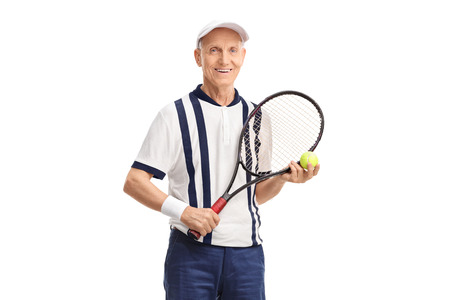 70s tennis: Senior with a racket and a tennis ball looking at the camera isolated on white background