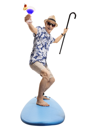 Full length portrait of an overjoyed senior with a cocktail and a cane standing on a surfboard isolated on white background