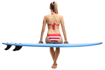 Rear view shot of a young woman in bikini sitting on a surfboard isolated on white background