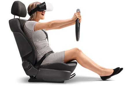 fastened: Woman with a VR headset sitting in a car seat and holding a steering wheel isolated on white background Stock Photo