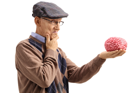 Pensive senior looking at a brain model isolated on white background Stock Photo