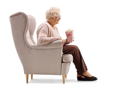 Mature woman with a box of  popcorn and 3D glasses seated in an armchair isolated on white background
