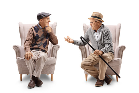 Two elderly men seated in armchairs talking with each other isolated on white background