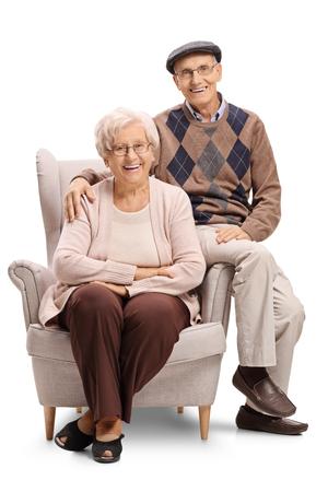 Ältere Paare , die in einem Lehnsessel sitzen und die Kamera lokalisiert auf weißem Hintergrund betrachten Standard-Bild