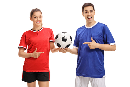 Female footballer and a male footballer holding a football and pointing isolated on white background Stock Photo