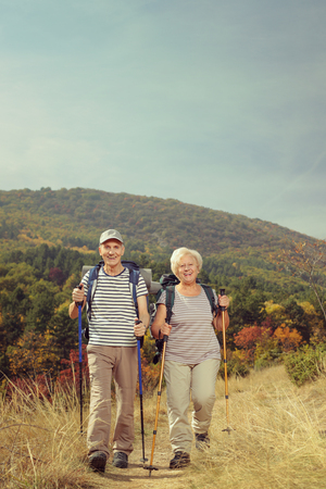 Full length portrait of two elderly hikers walking towards the camera outside