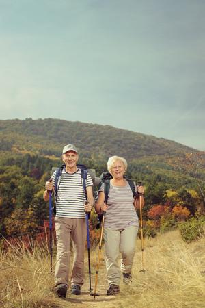 Volledig lengteportret van twee bejaarde wandelaars die naar de camera buiten lopen Stockfoto