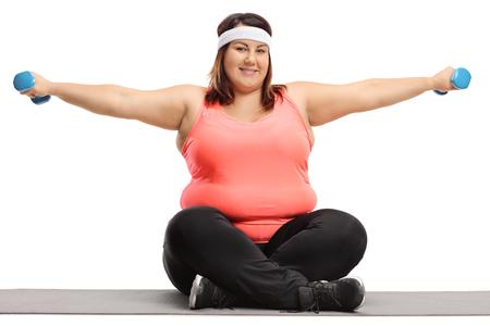 Donna di peso eccessivo seduta su una stuoia di esercitazione che si esercita con i piccoli dumbbells isolati su priorità bassa bianca