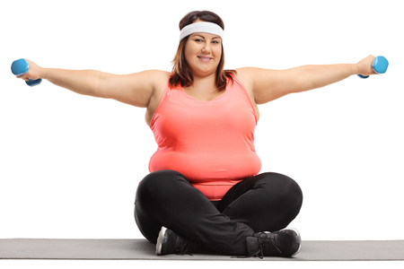 Overweight woman seated on an exercise mat exercising with small dumbbells isolated on white background