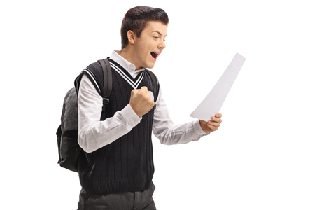 Teenage student looking at an exam and gesturing happiness isolated on white background