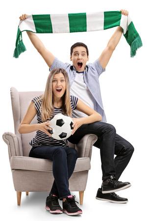 Opgewekte voetbalventilators die in een leunstoel en het toejuichen geïsoleerd op witte achtergrond zitten