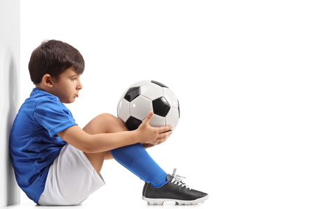 Disappointed little footballer leaning against a wall isolated on white background Foto de archivo