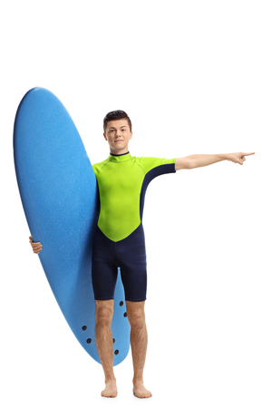 Full length portrait of a teenage surfer holding a surfboard and pointing isolated on white background Stock Photo