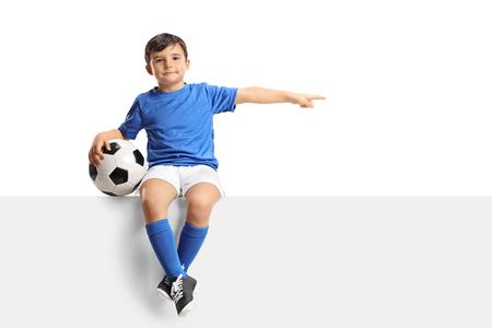 Piccolo calciatore che si siede su un pannello e che indica isolato su fondo bianco
