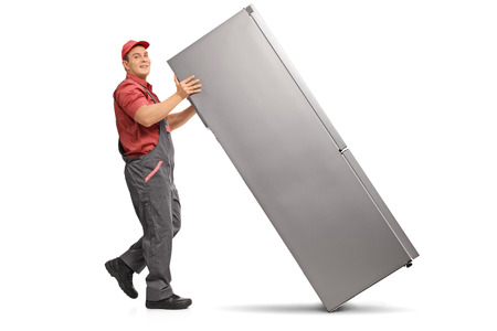 Full length profile of a repairman pushing a refrigerator isolated on white background Stock Photo
