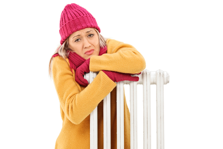 shiver: Freezing young woman leaning on a radiator isolated on white background Stock Photo