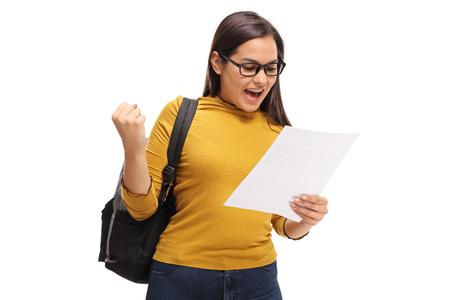 Vrouwelijke tiener student kijken naar een examen en gebaar geluk geïsoleerd op een witte achtergrond Stockfoto