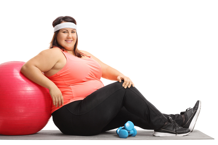 Übergewichtige Frau , die auf einer Übungsmatte sitzt und auf einem pilates Ball lokalisiert auf weißem Hintergrund lehnt