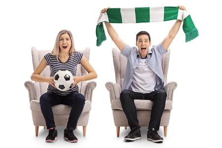 Excited soccer fans with a football and a scarf sitting in armchairs and cheering isolated on white background