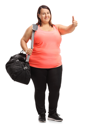 Full length portrait of an overweight woman with a sports bag making a thumb up gesture isolated on white background