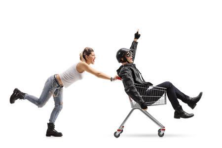Punk girl pushing a shopping cart with a biker riding inside and pointing up isolated on white background Stock Photo