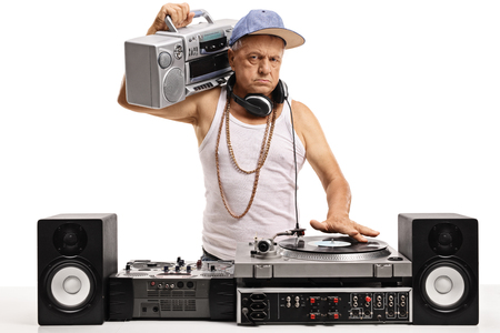Angry elderly DJ with a boombox playing music on a turntable isolated on white background Stock Photo