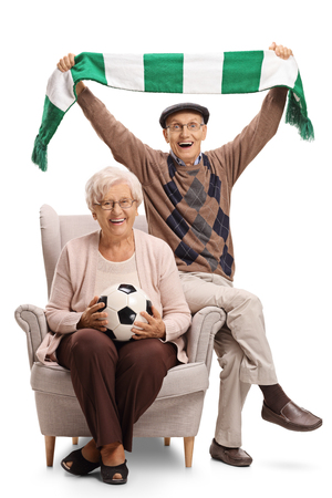 Overjoyed elderly soccer fans with a football and a scarf sitting in an armchair and cheering isolated on white background