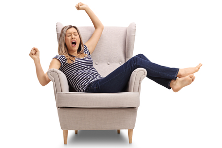 Tired young woman lying in an armchair and yawning isolated on white background