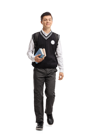 Full length portrait of a teenage student walking towards the camera isolated on white background