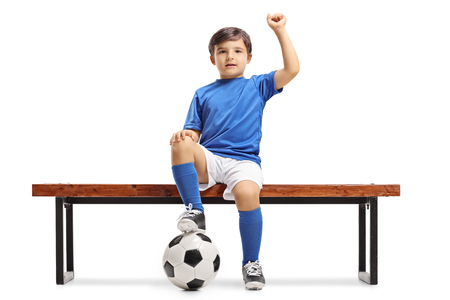 Little footballer sitting on a bench and gesturing happiness isolated on white background Stock Photo