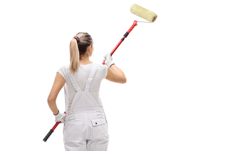 Rear shot of a female painter painting with a paint roller isolated on white background Banco de Imagens