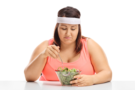 Sad overweight woman sitting at a table and looking at a bowl of salad isolated on white background Foto de archivo