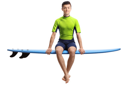 Teenage surfer seated on a surfboard isolated on white background Stock Photo