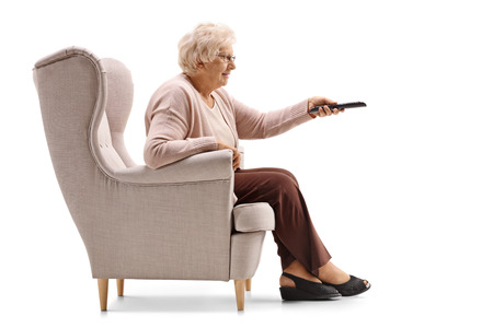 Elderly woman seated in an armchair changing channels on TV isolated on white background Stock Photo