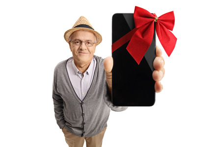 Mature man showing a phone wrapped with a red ribbon as a gift isolated on white background