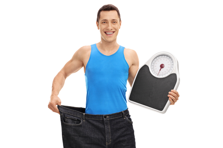 Guy in pair of oversized jeans holding a weight scale isolated on white background Foto de archivo