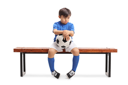 Sad little footballer sitting on a wooden bench isolated on white background