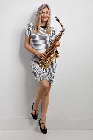 Full length portrait of a young woman holding a saxophone and leaning against a wall Foto de archivo