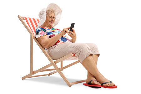 Elderly woman sitting in a deck chair and looking at a phone isolated on white background Stock Photo