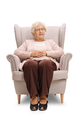 Elderly woman sitting in an armchair and looking at the camera isolated on white background