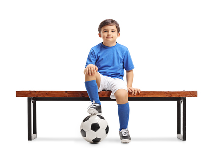 Little footballer sitting on a wooden bench and looking at the camera isolated on white background