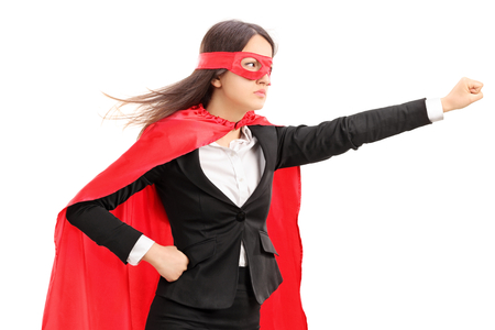Female superhero holding her fist in the air isolated on white background Banque d'images