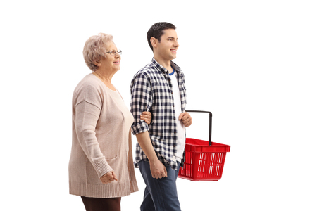 Mature woman walking with a young man holding an empty shopping basket isolated on white background Stock Photo