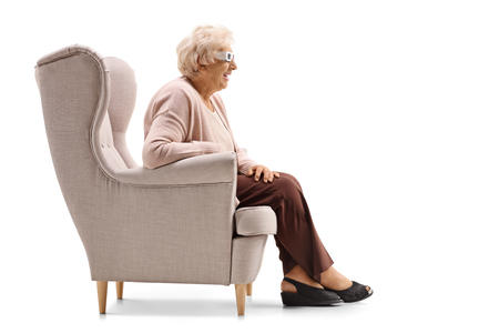 Senior lady with a pair of 3D glasses sitting in an armchair isolated on white background