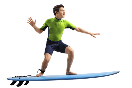 Teenager in a wetsuit surfing isolated on white background