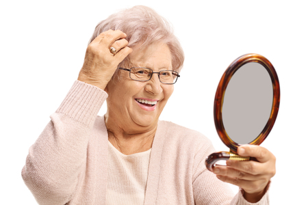 Elderly woman looking at herself in a mirror and making her hair isolated on white background Foto de archivo