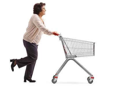 Foto de perfil completo de una anciana corriendo y empujando un carrito de compras vacío aislado sobre fondo blanco.