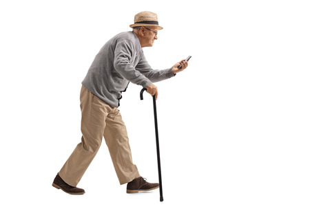 Full length profile shot of a senior with a cane walking and looking at a phone isolated on white background Stock Photo