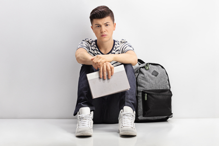 Sad teen student sitting on the floor and leaning against a wall Stock Photo
